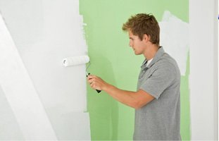 Painter painting the green wall of white
