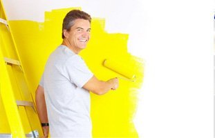 Painter painting the wall of yellow