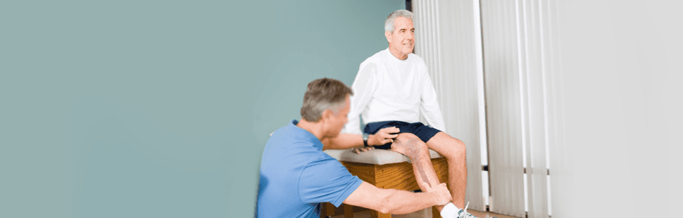 Doctor checking the injured leg of the old man