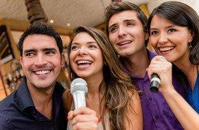 Friends having fun singing the karaoke machine