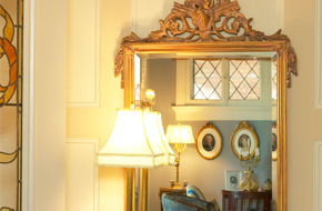 A glass mirror with near a lamp shade