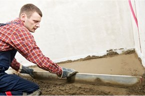 Man in red long sleeves shirt cementing the floor